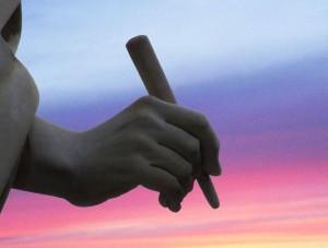 Hand met pen voor schrijven blog tegen gekleurde lucht als achtergrond
