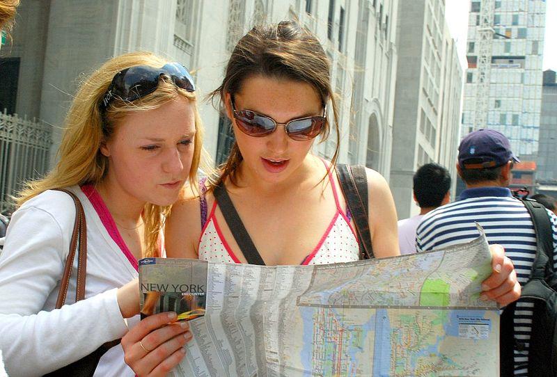 Twee meiden kijken op een kaart om samen de weg te bepalen